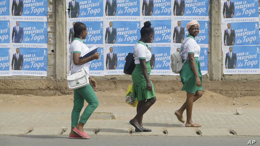 School girls walk past election posters of Togo's Incumbent President Faure Gnassingbe, Presidential Candidate of Union for the…