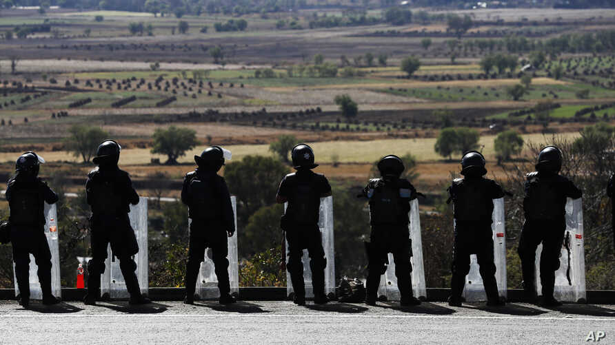 In this Feb. 6, 2020 photo, state police stand guard along the road leading into Uruapan, Michoacan state, Mexico. Uruapan, a…