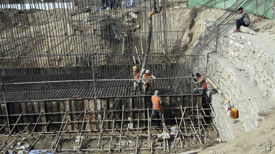 In this Monday, Feb. 10, 2020 photo, Afghan laborers work on a bridge project funded by the government, in Kabul, Afghanistan…