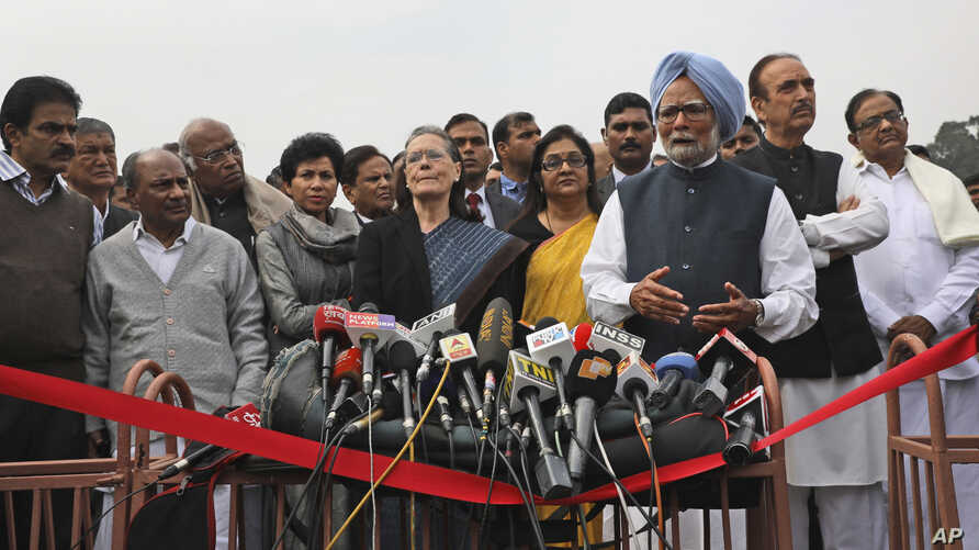 Former Indian prime Minister Manmohan Singh, center right, makes a press statement with Congress party President Sonia Gandhi,…