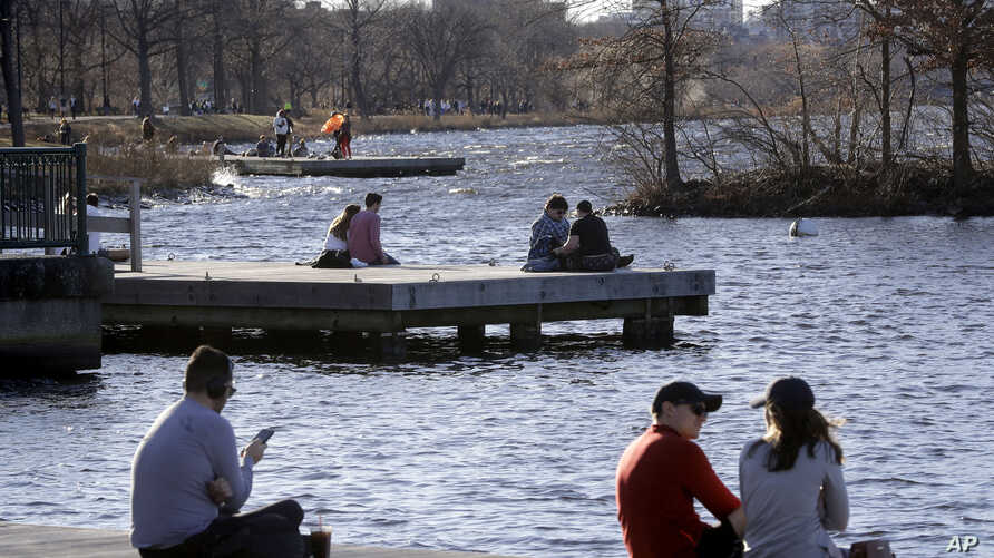 FILE - In this Sunday, Jan. 12, 2020 file photo, people sit on docks in the Charles River Esplanade park in Boston during…