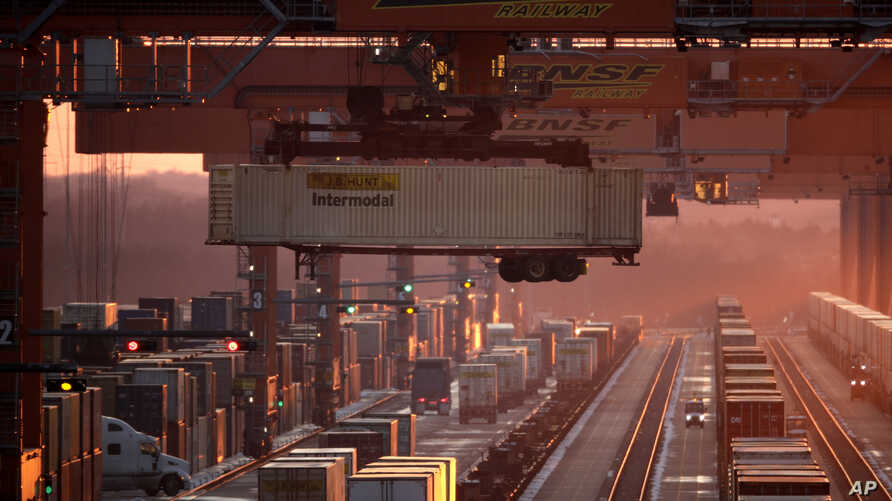 Shipping containers are offloaded at an a BNSF Railway intermodal facility as the sun sets Friday, Dec. 20, 2019, in Edgerton,…