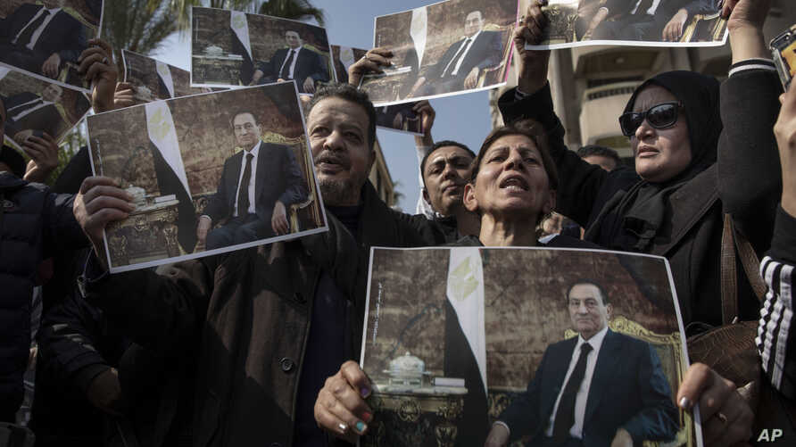 Supporters of ousted President Hosni Mubarak hold posters with his photograph near the cemetery where he will be buried, in the…