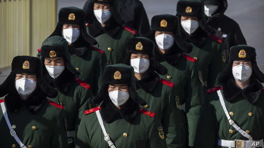 Paramilitary policemen wear face masks as they march in formation into a pedestrian underpass next to Tiananmen Square in…