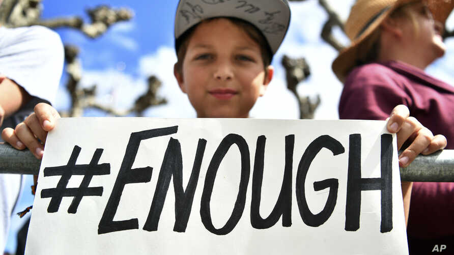 Zachary Chakin holds up a sign as crowds of people participate in the March for Our Lives rally in support of gun control,…