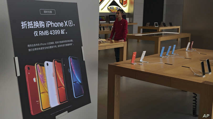 FILE - In this Jan. 3, 2019, file photo, a trade-in for iPhone XR promotion board is displayed as an Apple employee waits for…