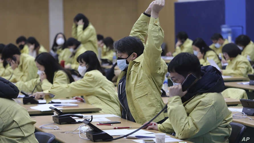 A government official wearing a face mask stretches as he and his colleagues make phone call to members of Shincheonji Church…