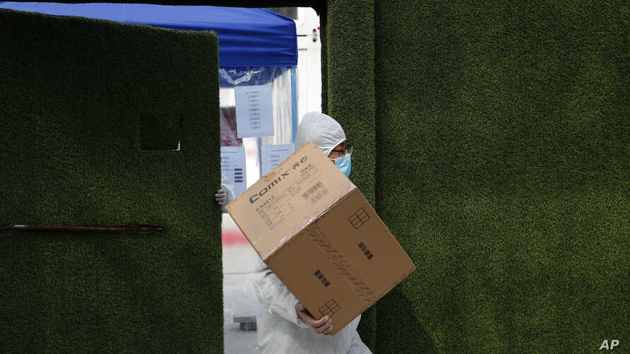 A worker wearing protective gear carries a box from an entrance gate to a pickup point outside a construction site at the…