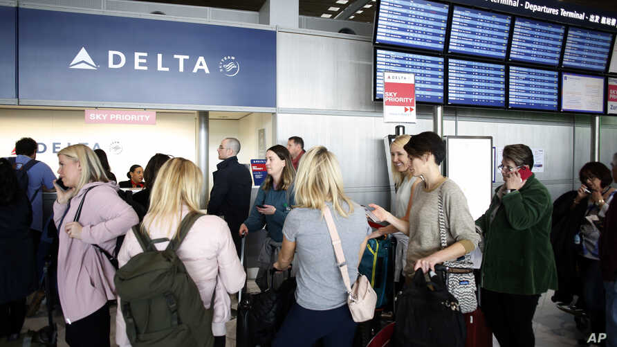 Passengers wait in front of the desk of American airline company 'Delta', at the Roissy Charles de Gaulle airport, north of…