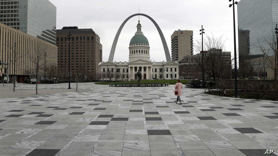 A pedestrian crosses a nearly empty Kiener Plaza Park Tuesday, March 17, 2020, in St. Louis. Activity in downtown St. Louis was…