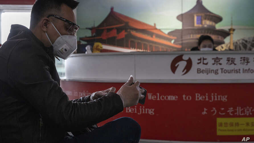 In this March 12, 2020, photo, a traveler waits near a tourist information booth at the Capital International Airport terminal…