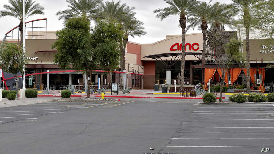 An empty parking lot leading to a closed AMC movie theatre and restaurants sits idly Wednesday, March 18, 2020, in Phoenix. The…