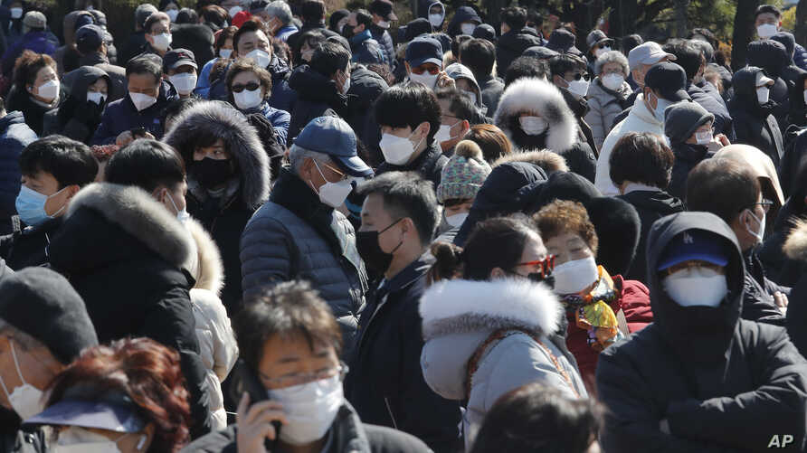 People line up to buy face masks to protect themselves from the new coronavirus outside Nonghyup Hanaro Mart in Seoul, South…