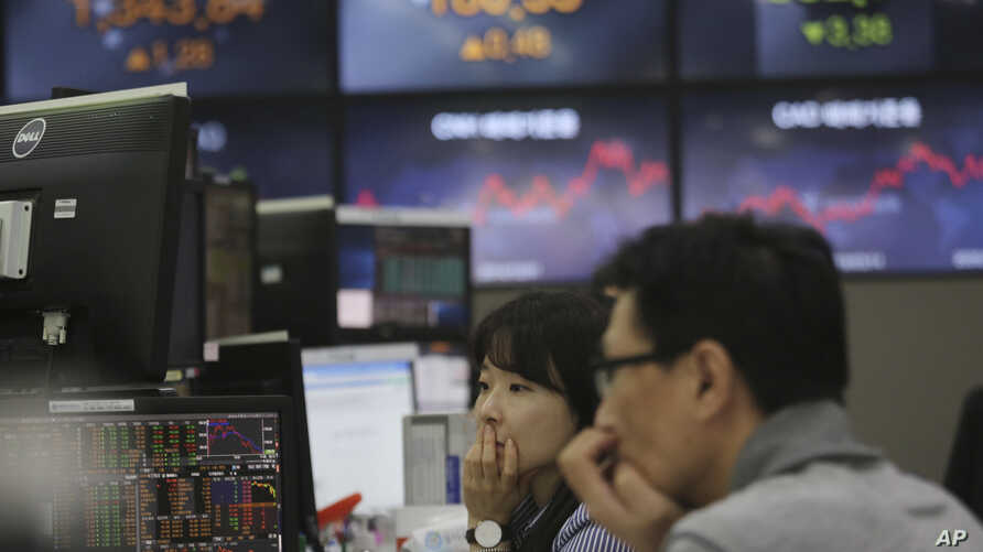 Currency traders watch monitors at the foreign exchange dealing room of the KEB Hana Bank headquarters in Seoul, South Korea,…