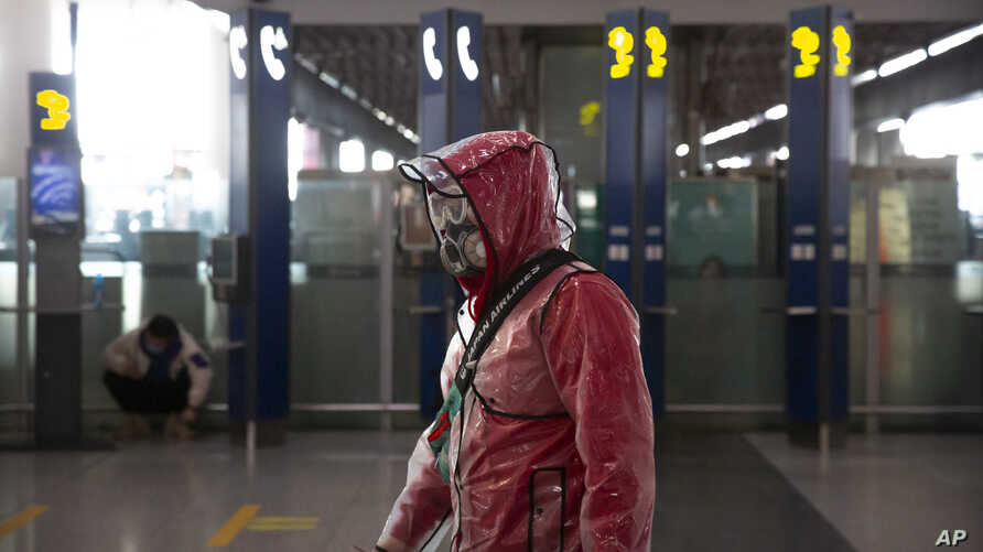 A traveler wears a respirator, goggles, and a raincoat as he walks through Beijing Capital International Airport in Beijing,…