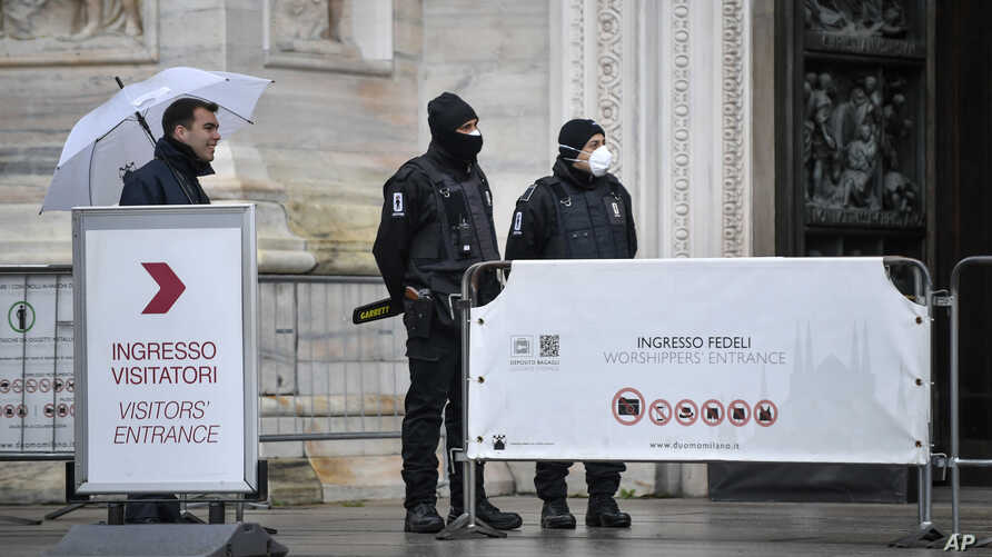 Personnel who perform security checks at the entrance of the Duomo gothic cathedral wear face masks as the Duomo reopened to…