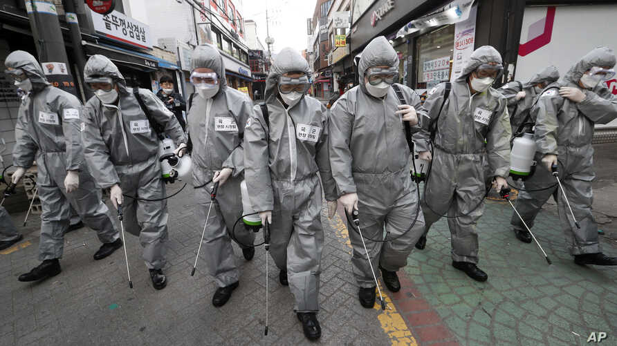 Army soldiers wearing protective suits spray disinfectant as a precaution against the new coronavirus at a shopping street in…