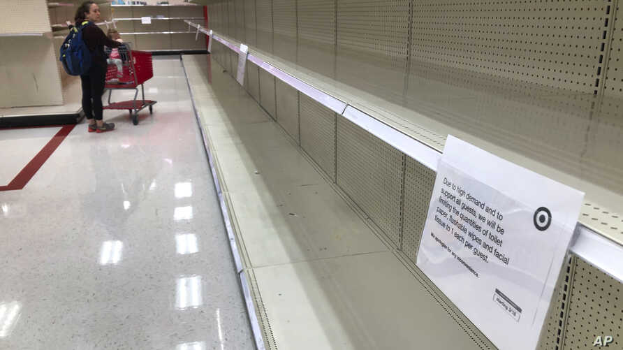 A woman looks at empty shelves in the paper goods section at a Target store Thursday, March 19, 2020, in Overland Park, Kan…