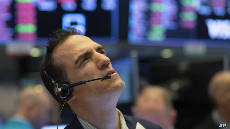 Stock trader Gregory Rowe works at the New York Stock Exchange, Wednesday, March 18, 2020 in New York. Global stock markets…