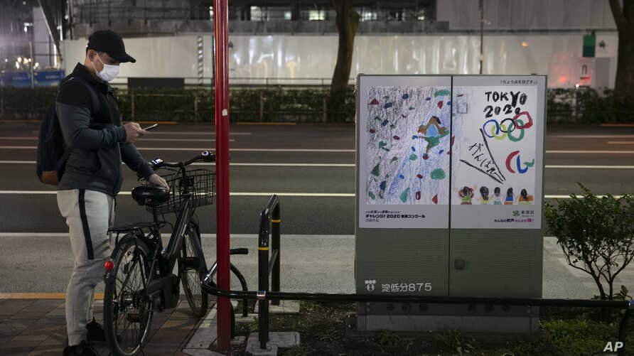A man wearing a mask looks at his smartphone next to a poster celebrating the Tokyo 2020 Olympics Tuesday, March 3, 2020, in…