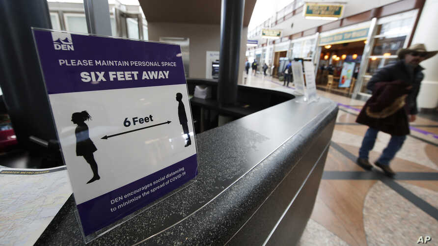 A sign advises travelers to keep their distance in Denver International Airport as travelers deal with the spread of…