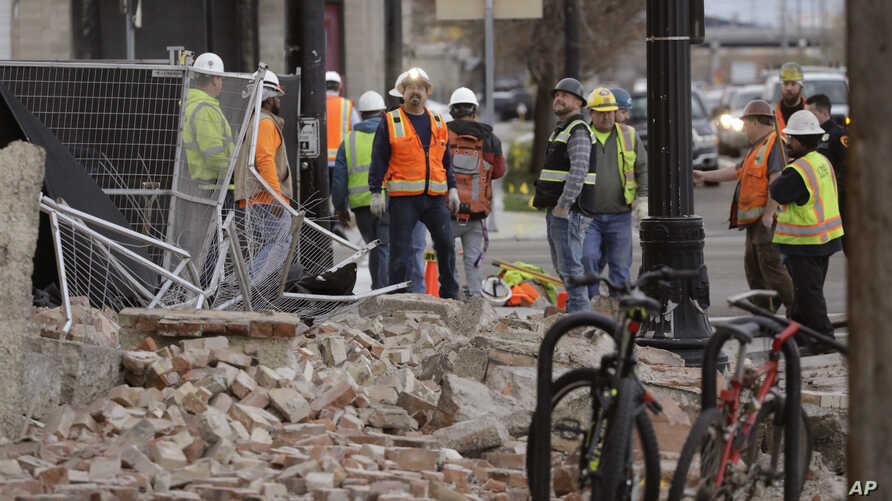 Construction workers looks at the rubble from a building after an earthquake Wednesday, March 18, 2020, in Salt Lake City.  A 5…