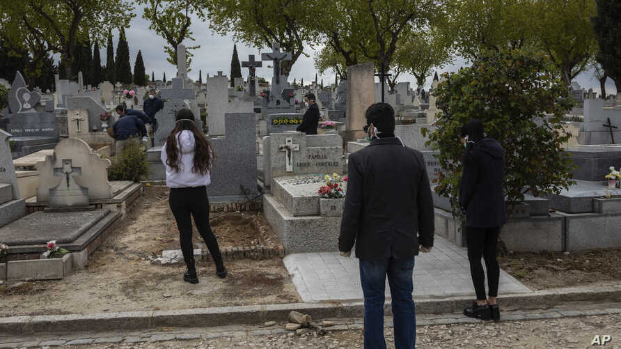 Relatives wearing face masks to protect against coronavirus, observe social distancing guidelines during a burial at a Madrid…