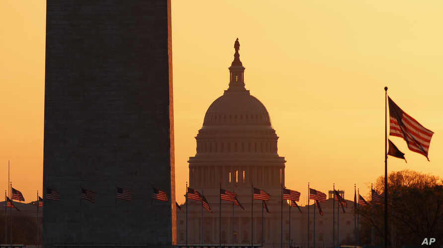 The Washington Monument and the U.S. Capitol are seen in Washington, at sunrise Wednesday, March 18, 2020. The White House has…