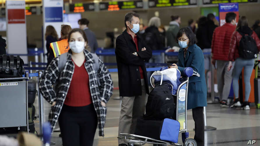 Travelers cover their faces with masks as they wait to drop their luggage at the Los Angeles International Airport Saturday,…