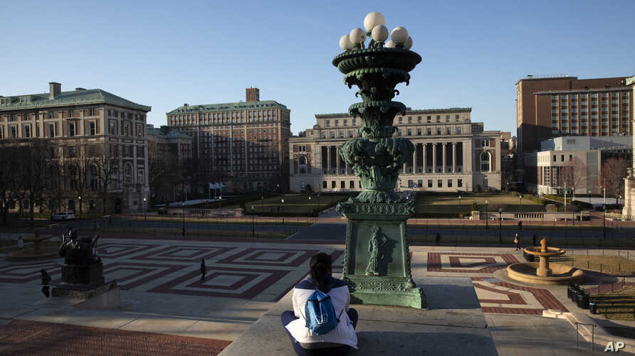 A woman sits on the Columbia University campus, Monday, March 9, 2020, in New York. The Ivy League school is canceling two days…