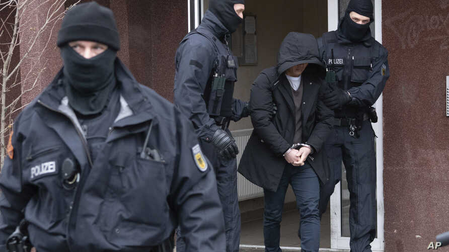 Police officers escort a suspect during a raid in Berlin, Germany, Tuesday, March 3, 2020. More than 700 police officers…