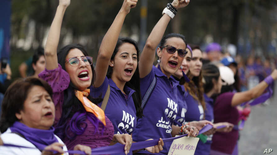 """Women chant as part of a """"human chain"""" of around 200 women calling for an end to gender violence, on the eve of International…"""