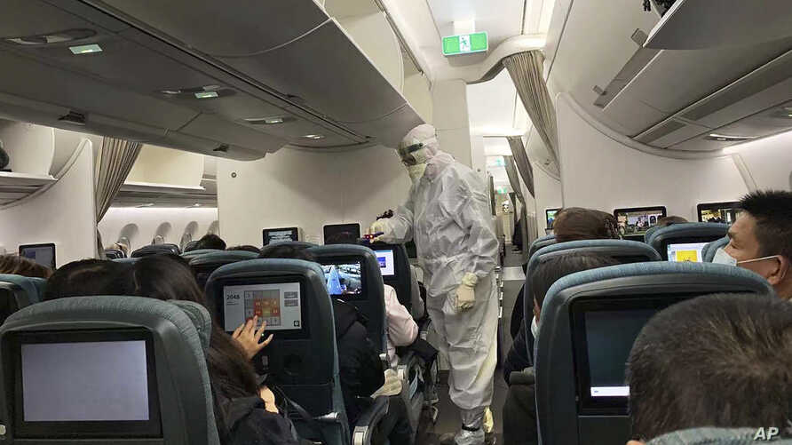 A worker in a hazardous materials suit takes the temperature of a passenger on a Cathay Pacific flight from Hong Kong to Rome…