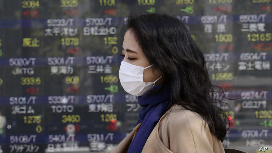 A woman walks by an electronic stock board of a securities firm in Tokyo, Wednesday, March 18, 2020. Major Asian stock markets…