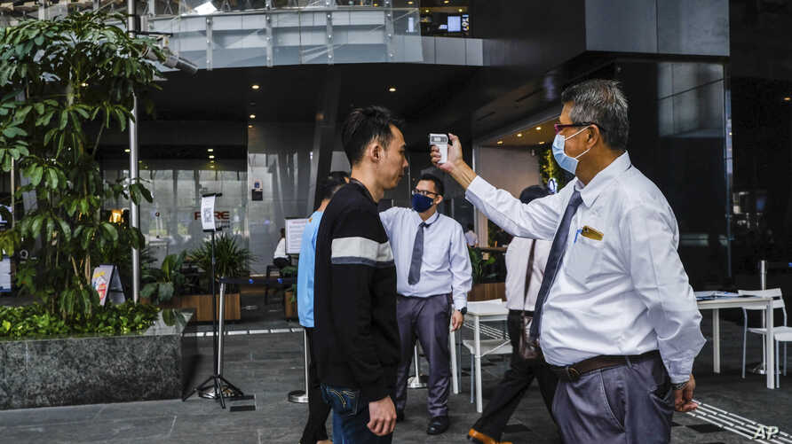 In this March 16, 2020, photo, a man scans a visitor's forehead to check his temperature before entering the Asia Square Tower…