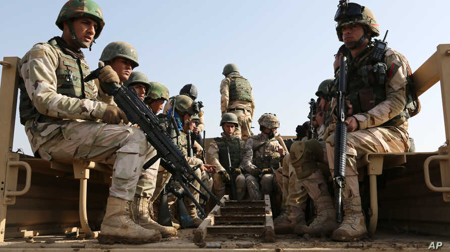 Iraqi soldiers sit in a vehicle during a training exercises at Basmaya base, 40 kilometers southeast of Baghdad, Iraq, Sunday,…