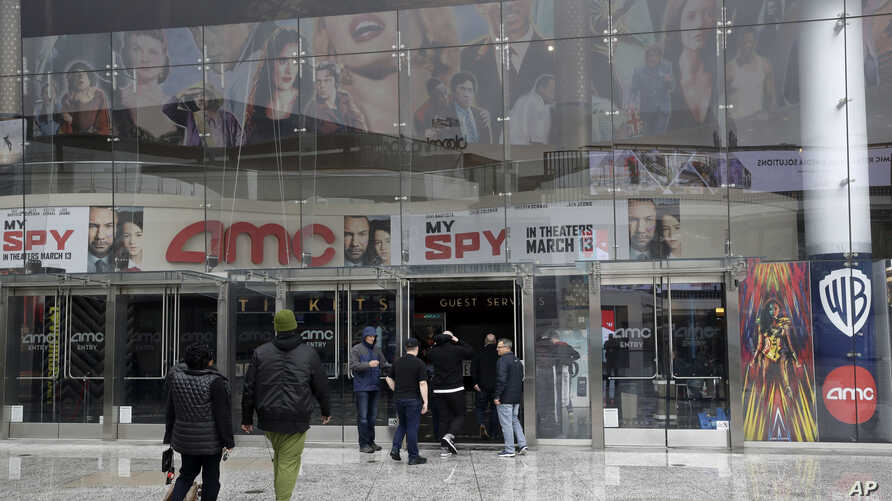 People enter an AMC theater Saturday, March 14, 2020, in Los Angeles. Californians wanting to escape the new reality of the…