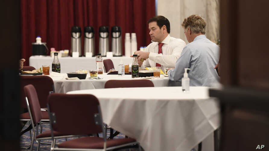 In this March 20, 2020, photo Sen. Rand Paul, R-Ky., right, Sen. Marco Rubio, R-Fla., left, have lunch at a Republican policy…
