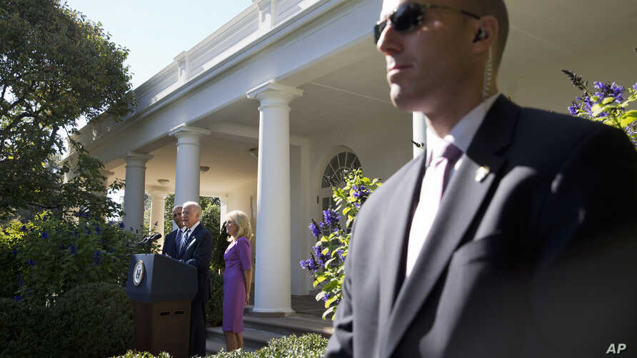 A Secret Service Agent stands guard as Vice President Joe Biden, with President Barack Obama and his wife Jill Biden, speaks in…