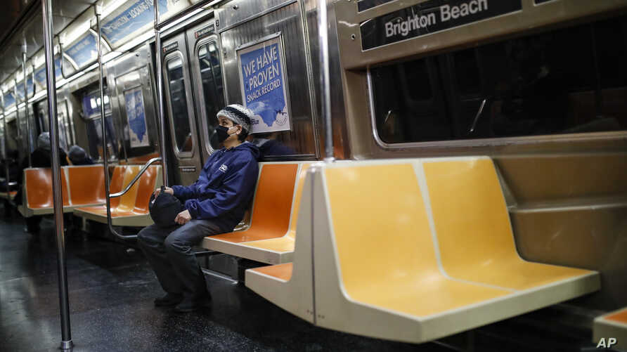 A commuter wears a face mask while riding the a nearly empty subway car into Brooklyn, Thursday, March 12, 2020, in New York…