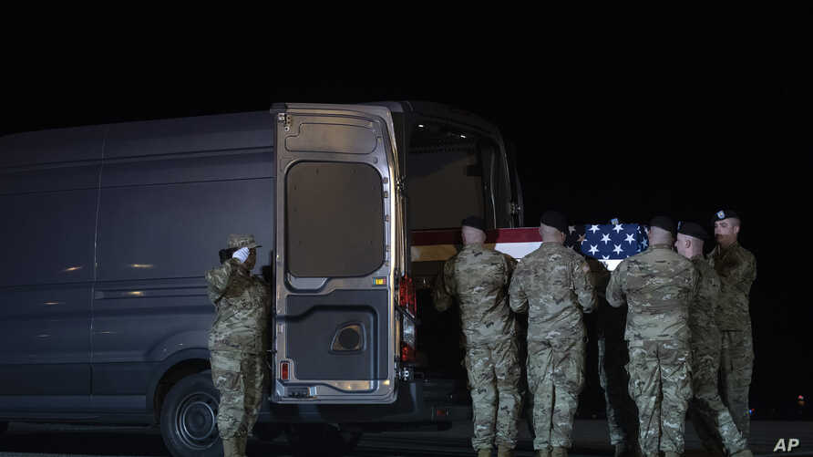 An Army carry team places the transfer case containing the remains of Army Spc. Juan Miguel Mendez Covarrubias, 27, from…