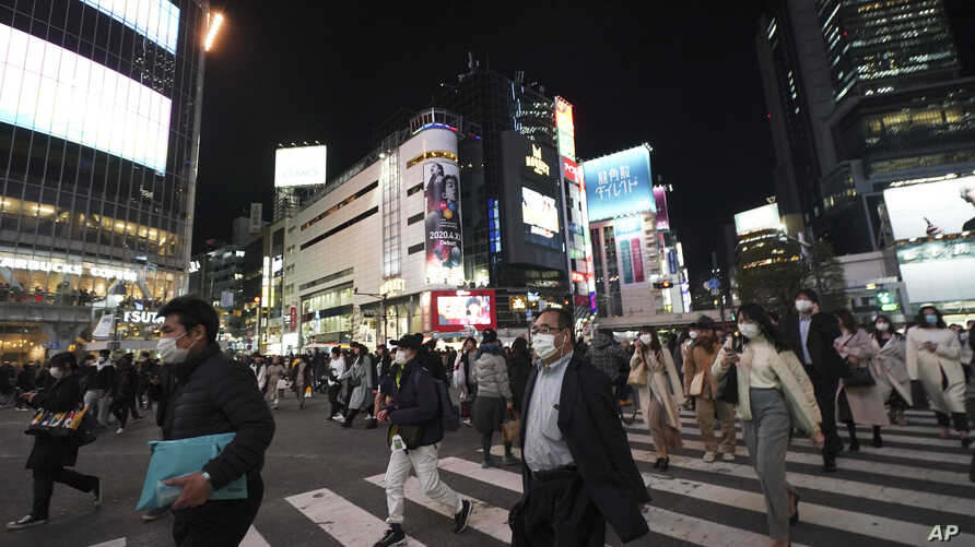 Pedestrians wear face masks in hopes of preventing the spread of the coronavirus walk through a crossing in the Shibuya…