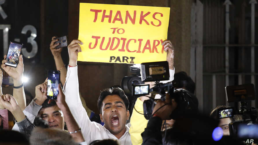 Indians holds banners and shout slogans outside Tihar central prison in New Delhi, India, Friday, March 20, 2020. Four men were…