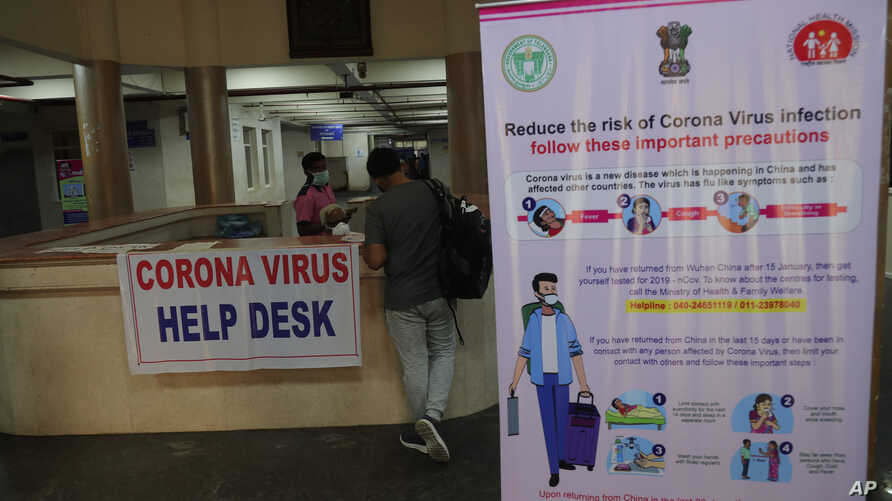 An Indian man with symptoms fills a form at a Corona virus help desk at the Government Gandhi Hospital in Hyderabad, India,…
