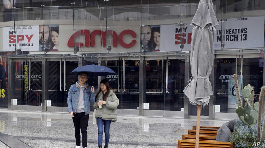 People exit an AMC theater Saturday, March 14, 2020, in Los Angeles. Californians wanting to escape the new reality of the…