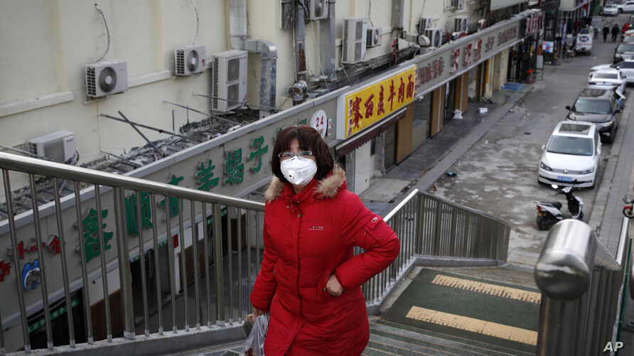 A woman wearing a protective face mask walks past closed restaurants following the coronavirus outbreak in Beijing, Monday,…