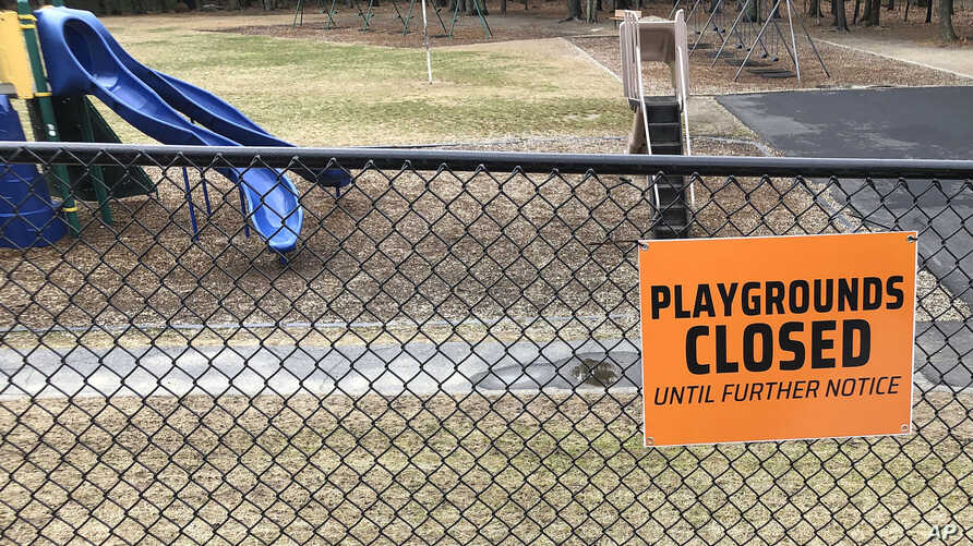 FILE - This Friday, March 20, 2020 file photo shows a closed sign near an entrance to a playground at an elementary school in…