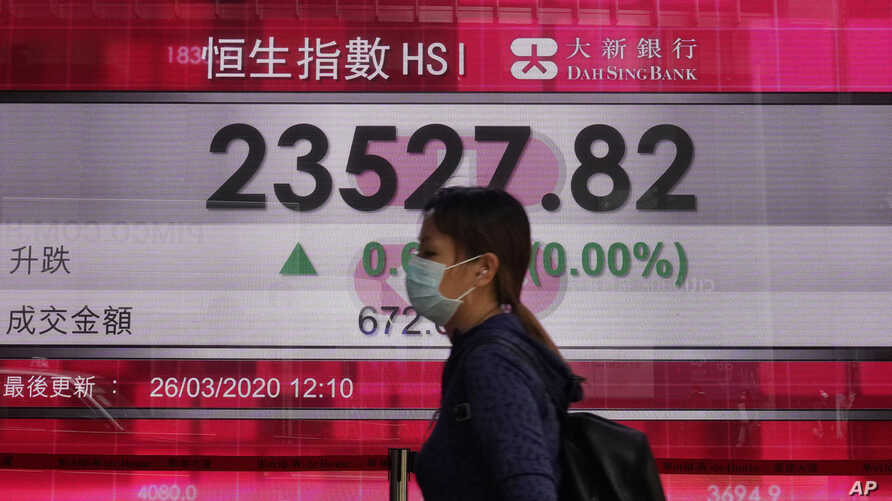A woman wearing face mask walks past a bank electronic board showing the Hong Kong share index at Hong Kong Stock Exchange…