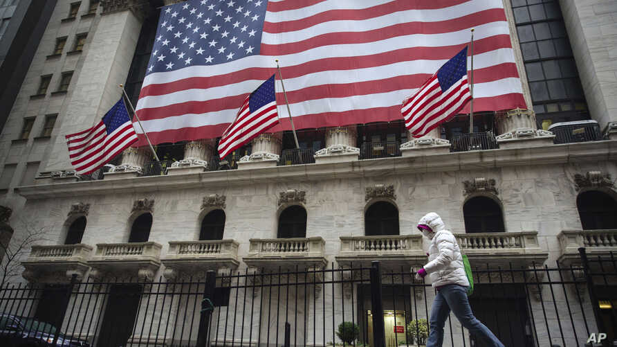 A pedestrian wearing a surgical mask and gloves walks past the New York Stock Exchange on Thursday, March 19, 2020, in New York…