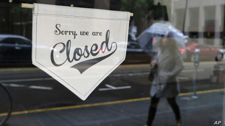 A woman walks along through the Financial District past the closed Homage Ltd. restaurant which is normally open for breakfast…